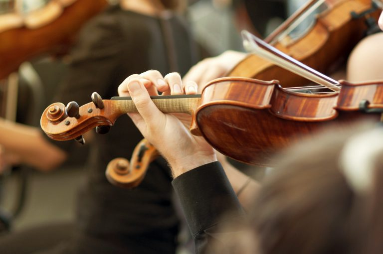 Member of classical music orchestra playing violin on a concert